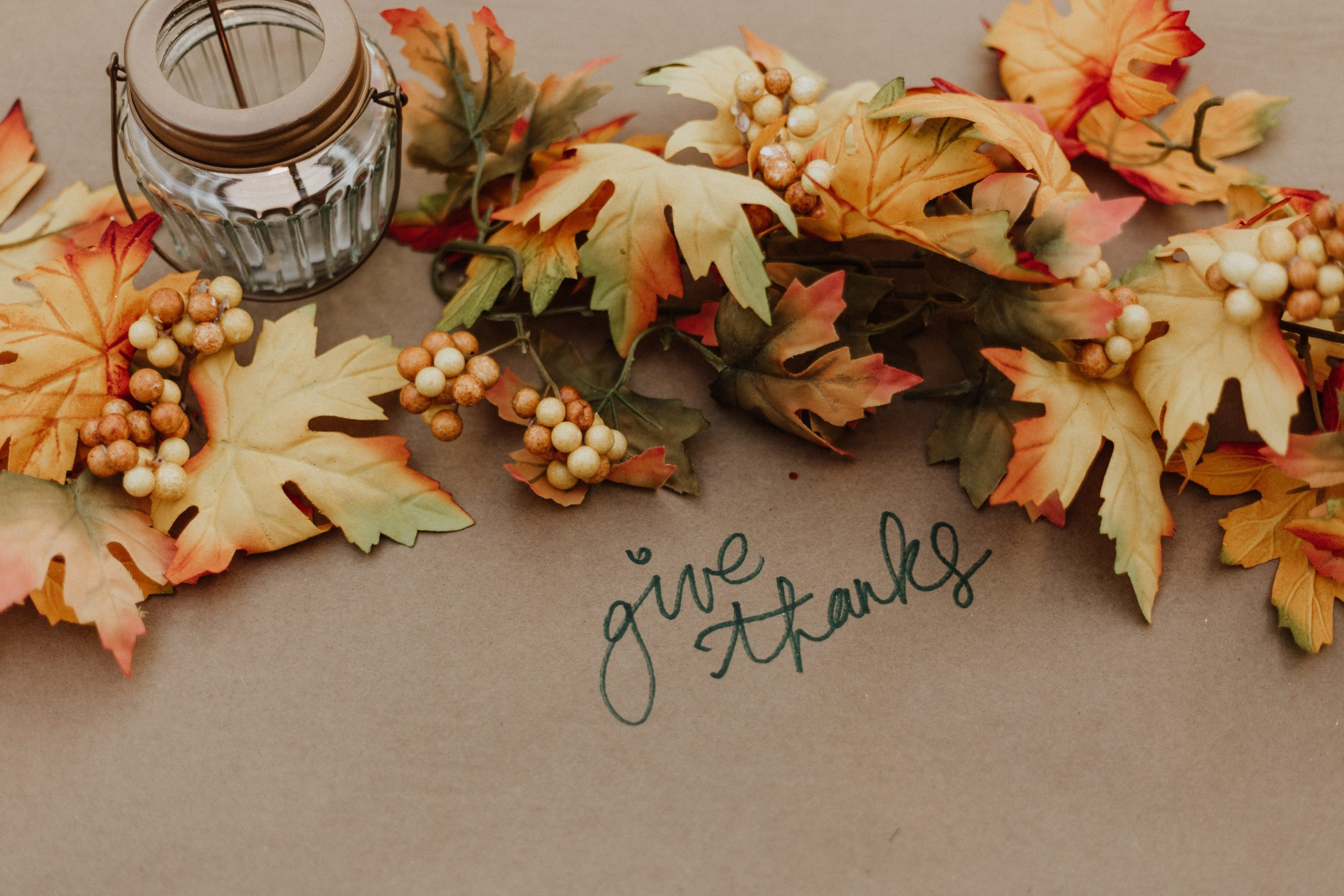 """pile of leaves and a candle laid on brown craft paper with the phrase """"give thanks"""" written in marker on the paper. There are many misconceptions around mental health during the holidays. Mental health is important year round, but some may encounter stressors that trigger the holidays blues. Take care of your holiday mental health by engaging in activities with family, and much more."""