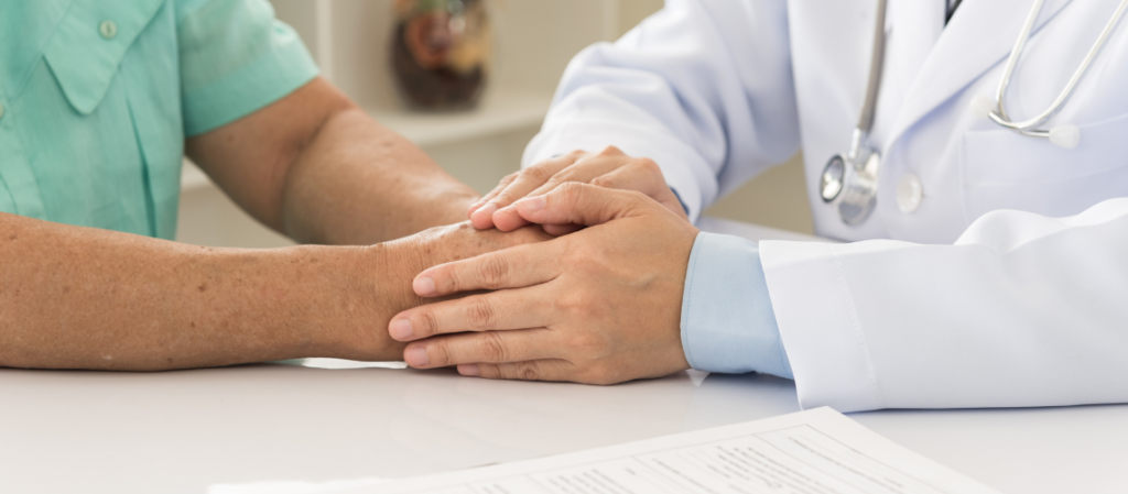 Doctor holding patient's hands as he delivers diagnosis.