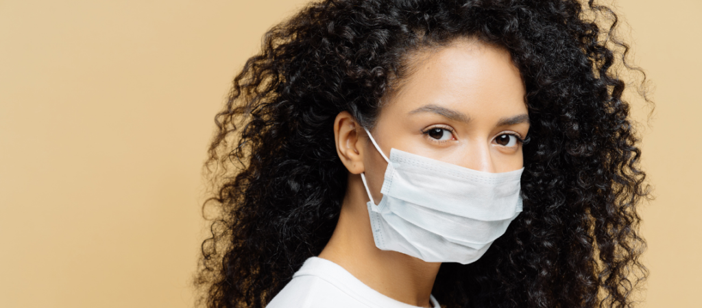 Woman wearing surgical mask protecting herself and others from COVID-19.