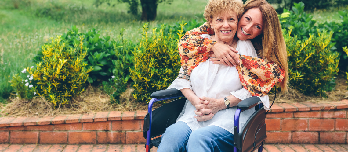 Elderly mother in a wheelchair being hugged by her daughter. Article discussing dementia and how to protect loved ones diagnosed.